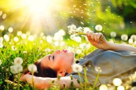 Kvinna ligger i gräset en solig dag och blåser maskrosfrön.